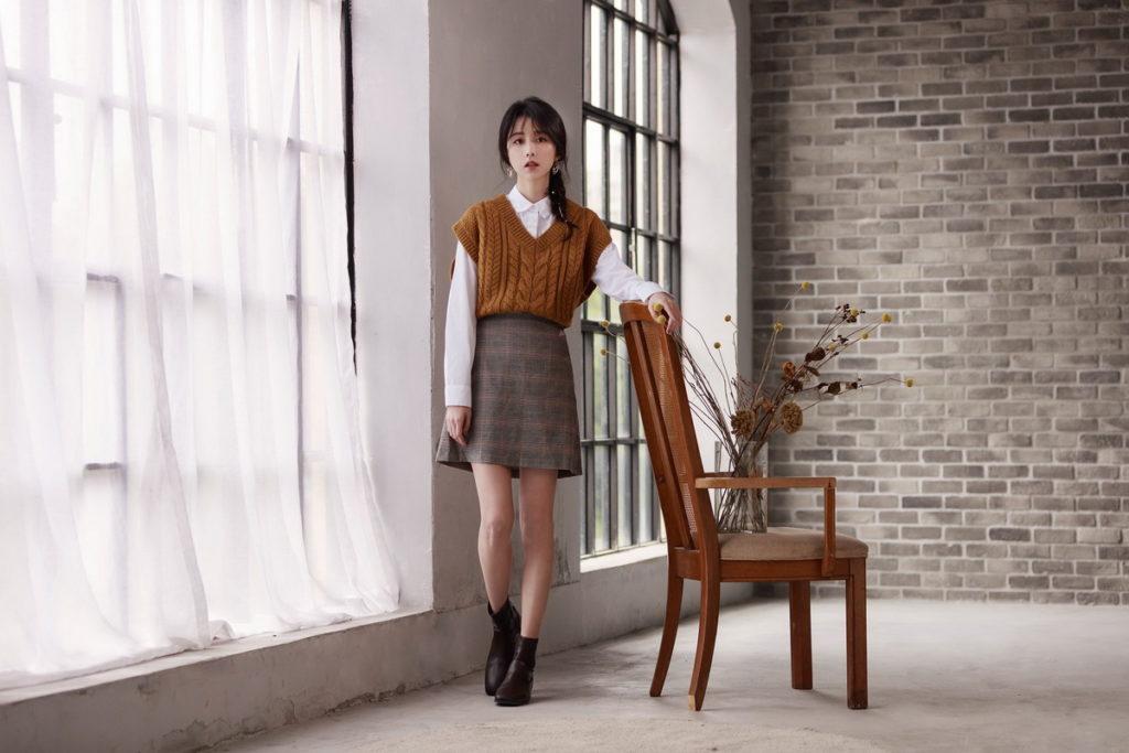 GU「品牌好友」邵雨薇本次以褐色的「短版粗紡針織背心」搭配經典長袖白襯衫以及格紋迷你裙,展現氣質甜美的零失誤好感穿搭。