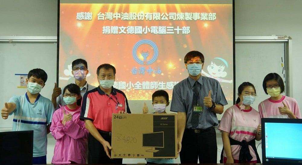 可能是 8 個人、大家站著和顯示的文字是「感謝 台灣中油股份有限公司煉製事業部 捐贈文德國小電腦三十部 台灣中油 夢國小全體師生感」的圖像
