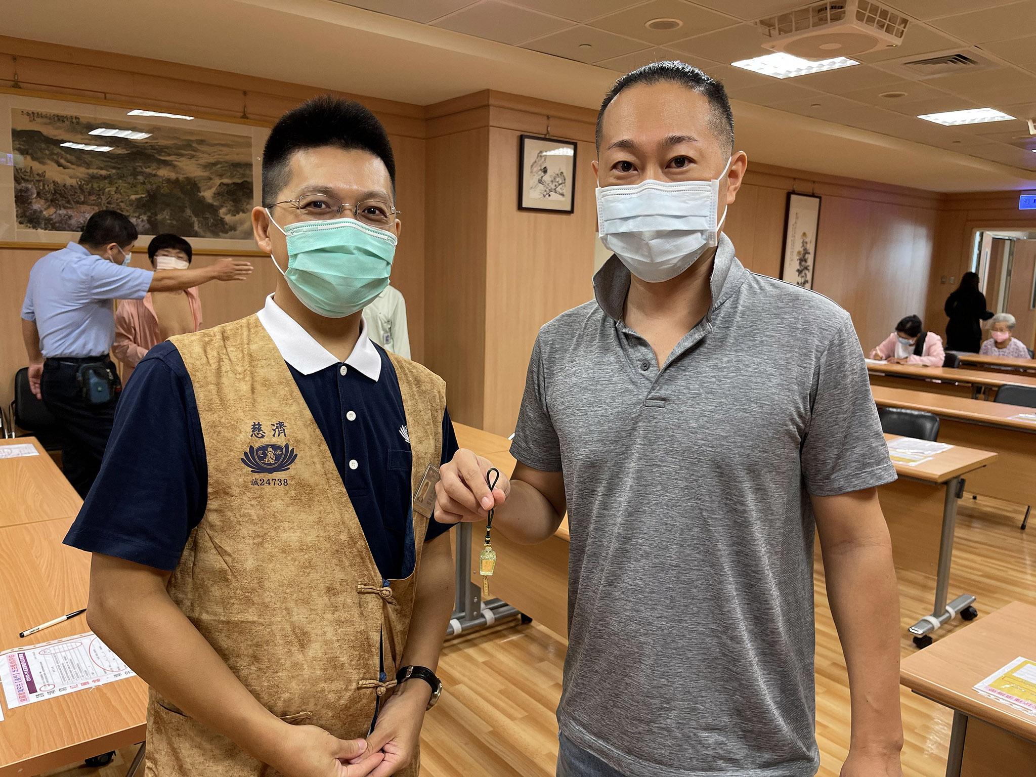 市川先生(右)獲贈靜思祈福心燈吊飾,特地與日語志工劉奕男師兄(左)合影。